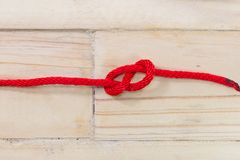 Zahl-acht Knoten gemacht mit rotem Seil auf hölzernem Hintergrund Stockfoto
