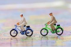 Zahl businessmans, die auf der Weltkarte radfahren Stockbilder