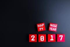 Zahl des guten Rutsch ins Neue Jahr 2017 auf roten Papierkastenwürfeln auf schwarzem backg Lizenzfreie Stockfotografie
