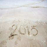 Zahl des Jahres 2015 geschrieben auf Hintergrund 2015 des sandigen Strandes/des neuen Jahres Stockfoto