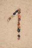 Zahl des Kiesels 1 auf selektivem Fokus des Sandes Stockfotos