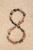 Zahl des Kiesels 8 auf selektivem Fokus des Sandes Stockbilder
