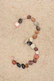 Zahl des Kiesels 3 auf selektivem Fokus des Sandes Stockfoto