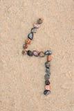Zahl des Kiesels 4 auf selektivem Fokus des Sandes Stockbilder
