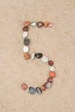 Zahl des Kiesels 5 auf selektivem Fokus des Sandes Stockfotos