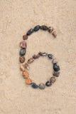 Zahl des Kiesels 6 auf selektivem Fokus des Sandes Stockbilder