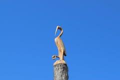 Zahl des Kranes auf dem Stumpf eines Baums gegen den blauen Himmel Zahlen von den Tieren gemacht vom Holz woodcarving Stockbild