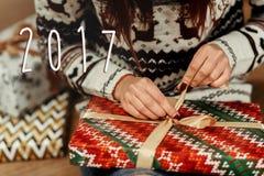 Zahl des neuen Jahres des Zeichens mit 2017 Texten auf der Frau, die Weihnachten-pres einwickelt Lizenzfreie Stockfotografie