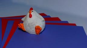 Zahl einer weißen Henne auf farbigem Papier stockfoto