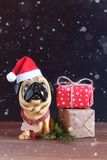 Zahl eines Hundes in einem Weihnachtshut auf einem Holztisch Symbol des kommenden Jahres Lizenzfreie Stockfotografie
