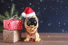 Zahl eines Hundes im Weihnachtshut auf einem Holztisch Symbol des neuen Jahres Stockfoto