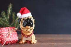 Zahl eines Hundes im Weihnachtshut auf einem Holztisch Symbol des neuen Jahres Lizenzfreies Stockfoto