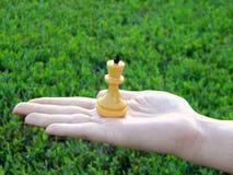 Zahl eines Schachkönigs auf einer weiblichen Hand Lizenzfreies Stockbild