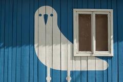 Zahl eines weißen Vogels auf einer hölzernen blauen Wand mit einem Fenster Lizenzfreie Stockfotos