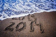 Zahlen auf dem Strand wäscht sich weg durch eine Welle Stockbild