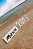 2015 Zahlen des neuen Jahres auf dem Strand und dem Zeichen WILLKOMMEN Lizenzfreies Stockbild