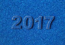 Zahlen des neuen Jahres 2017 ausgebreitet auf Hintergrund von funkelnden glänzenden Pailletten des Blaus Lizenzfreies Stockfoto