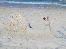 Zahlen des Sandes und der Oberteile auf dem Strand gegen das Meer lizenzfreie stockfotografie