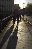 Zahlen, die über eine Brücke, lange Schatten gehen Stockfoto