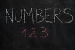 Zahlen fassen und erste drei Buchstaben auf schwarzer Tafel ab Stockfotografie