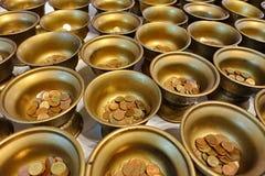 Zahlen Sie Münzen in 109 Mönchschüsseln auf buddhistische Anbetungsart Stockbild