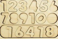 Zahlen von 1 bis 9 herausgeschnitten auf einem hölzernen Brett stockfotografie