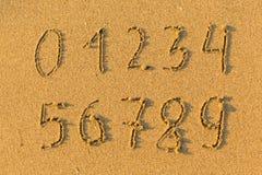 Zahlen von 0 bis 9 von Hand gezeichnet im Strandsand Auszug Stockfotos