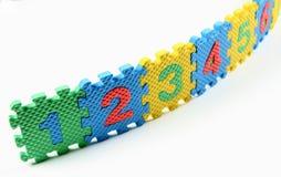 Zahlpuzzlespiele ordneten in einer Reihe an stockfotografie