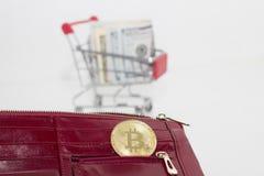 Zahlung durch cryptocurrency Bitcoin oder Dollar bitcoin Münze in der roten Geldbörse lizenzfreies stockbild