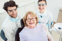 Zahnärzte und Patient in der Chirurgie, die Kamera betrachtet Stockbilder