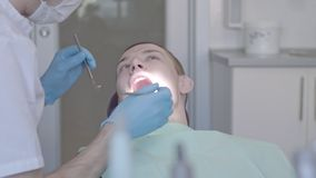 Zahnarzt überprüft die Mundhöhle des Patienten stock video