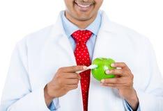 Zahnarzt, der Apfel und Zahnbürste zeigt lizenzfreies stockfoto