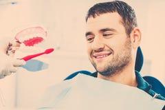 Zahnarzt, der dem Mannpatienten zeigt, wie man Zähne säubert Lizenzfreie Stockfotografie