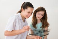 Zahnarzt, der dem Patienten Röntgenstrahl zeigt lizenzfreie stockbilder