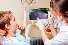 Zahnarzt, der die Details einer Röntgenstrahlabbildung erklärt Lizenzfreies Stockfoto