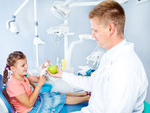 Zahnarzt, der einen Apfel gibt Lizenzfreie Stockfotos