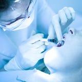 Zahnarzt, der einen weiblichen Patienten kuriert Lizenzfreie Stockfotos