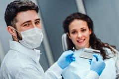 Zahnarzt, der Farbe von junge Frau ` s Z?hnen ?berpr?ft und vorw?hlt Junge Frau, die Farbe von Zähnen am Zahnarzt Choose die Farb stockfoto