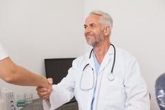 Zahnarzt, der Hände mit seinem Patienten rüttelt Lizenzfreies Stockfoto