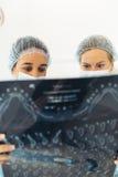 Zahnarzt, der ihrem Kollegen auf Röntgenstrahlbild etwas zeigt Lizenzfreie Stockfotos