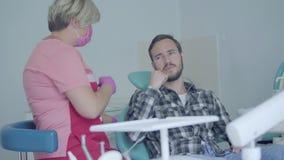 Zahnarzt in der medizinischen Maske und Handschuhe, die den Patienten für Inspektion vorbereiten Mann, der sein Problem erklärt,  stock video footage