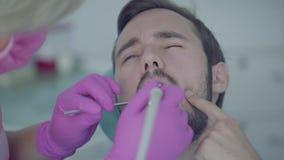Zahnarzt in der medizinischen Maske und Handschuhe, welche die tooths des Patienten verwendet medizinische Werkzeuge überprüfen W stock video footage