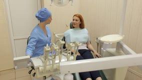 Zahnarzt, der mit einem Mädchenpatienten in der Klinik spricht stock footage