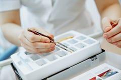 Zahnarzt, der mit Gebissen in seinem Laborb?ro arbeitet stockfotografie