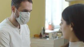 Zahnarzt, der mit jungem schönem Mädchen vor Behandlung spricht stock video