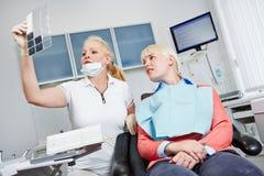 Zahnarzt, der Röntgenstrahlbild von Zähnen betrachtet Lizenzfreie Stockfotos