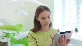 Zahnarzt, der an Tabletten-PC im zahnmedizinischen Büro arbeitet Gesundheitswesenarbeitskraft, die Tablette verwendet stock footage