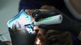 Zahnarzt, der Verfahren mit zahnmedizinischem kurierendem UV-Licht in der Klinik tut stock video