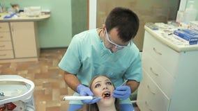 Zahnarzt, der zahnmedizinische kurierende UVlampe auf Zähnen des Patienten verwendet stock video footage