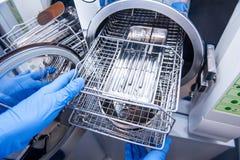 Zahnarzt gehen behilfliche ` s Hände entkeimende medizinische Instrumente vom Autoklav hinaus Selektiver Fokus Lizenzfreie Stockbilder
